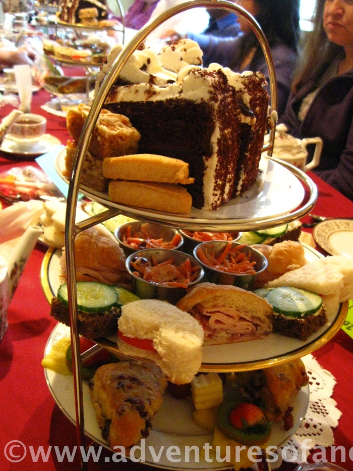 On the middle tier was the savory, consisting mostly of a variety of finger sandwiches, including the famous (and, in the American mind at least, quintessentially British) cucumber. On the bottom tier were what the menu listed as English Manor scones. These were served with two things I'd never tasted, although I'd read about them in books: clotted cream and lemon curd. All I can say is, despite their less-than-appetizing names, once you taste them, there's no going back. We had to ask the poor waitress to refill those dishes at least quite. The jam, though lovely, was forgotten. There were also sweet breads (not sweetbreads), fruit and cheese and, on the top tier, what me might call the crowning glory: the read sweets. I don't know what was more decadent, the rich chocolate cake or the shortbread (I'll go for the shortbread every time, if forced to choose, but that's just me. Any chocolate lover would consider me a madwoman for saying so).